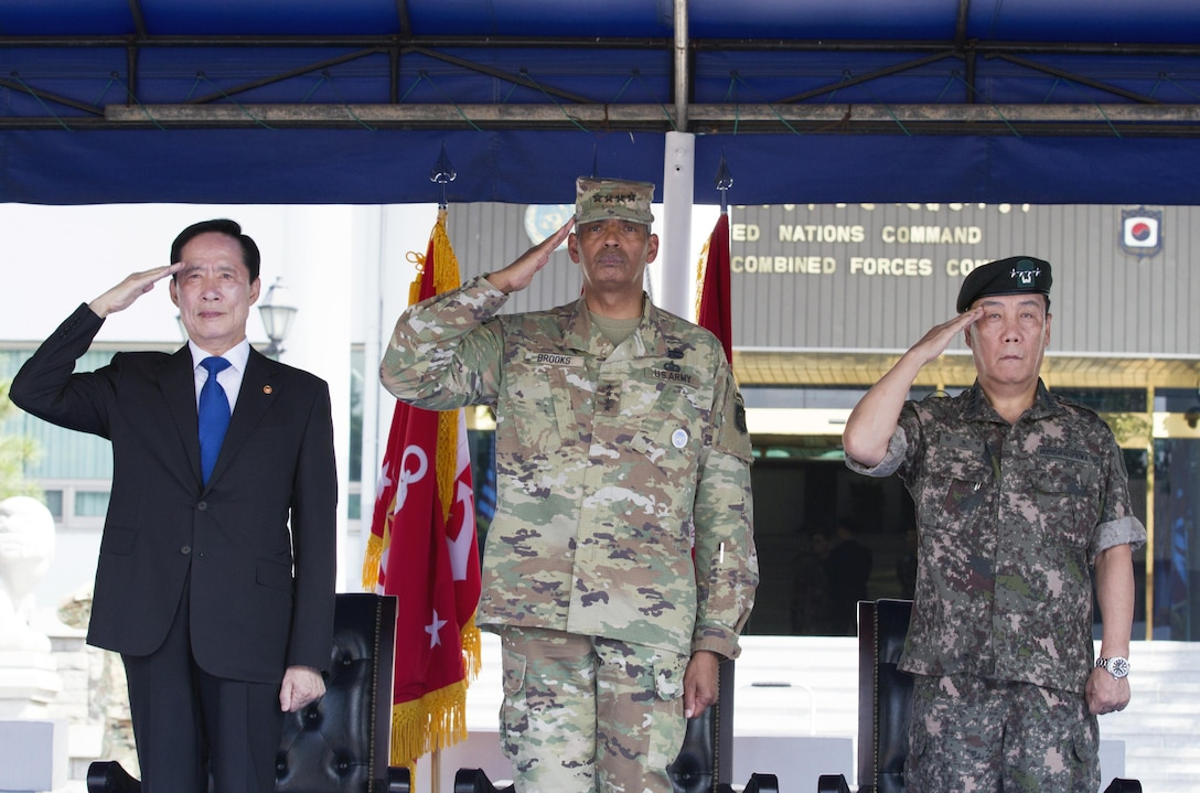 From left, Republic of Korea Minister of National Defense Song, Young-moo, General Vincent K. Brooks, commander of United Nations Command, Combined Forces Command and United States Forces Korea, and Gen. Leem Ho-young, deputy commander of CFC, render the appropriate honors during a ceremony at U.S. Army Garrison Yongsan, Republic of Korea, Aug. 4. The visit was the Honorable Song's first time to USFK headquarters since taking over as the MINDEF July 14. The ceremony included an inspection of the troops, a 19-gun salute and a presentation of one of the shell casings to honor the MINDEF.