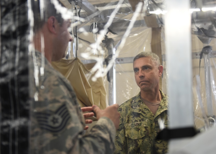 Tech. Sgt. Aaron De L'etoile, left, 628th Medical Group noncommissioned officer in charge of medical maintenance, showcases the Transportation Isolation System Aug. 1 to Rear Adm. Peter Clarke, right, U.S. Transportation Command Strategy, Capabilities, Policy and Logistics Directorate incoming director, during a demonstration as part of an orientation visit here. The TIS is designed to provide aeromedical evacuation for patients with known or suspected exposure to a contagious or infectious disease while protecting aircraft and aircrew. It provides worldwide patient transport capability in case of a biological event. USTRANSCOM is a unified, functional combatant command which provides support to the eight other U.S. combatant commands, the military services, defense agencies and other government organizations by providing full-spectrum global mobility solutions and related enabling capabilities for supported customers' requirements in peace and war.