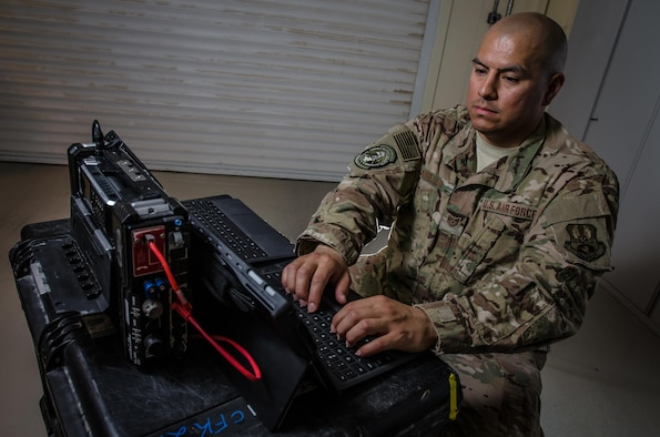 U.S. Air Force Tech. Sgt. Albert Cabello,the 609th Expeditionary Air and Space Communications Squadron NCO in charge of executive communications at the Combined Air Operations Center, tests the new executive  communications kit Aug. 1, 2017, at Al Udeid Air Base, Qatar. Cabello uses the kit to provide secure command and control network communications for key Air Force leaders via commercial medians and to establish voice, video, e-mail, and data services. (U.S. Air Force photo by Staff Sgt. Alexander W. Riedel)