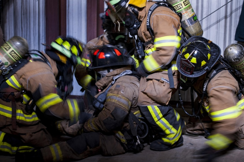 Firefighters from the 23d Civil Engineer Squadron rescue a simulated victim during rapid intervention fire training, Aug. 2, 2017, at Moody Air Force Base, Ga. Rapid intervention refers to the rescue of downed firefighters when they find themselves in trouble. During the course, Moody firefighters, as well as a Lowndes County firefighter, learned how to perform self-rescue, team rescue, and basic skills such as CPR and various carries in order to transport victims. (U.S. Air Force photo by Airman 1st Class Lauren M. Sprunk)
