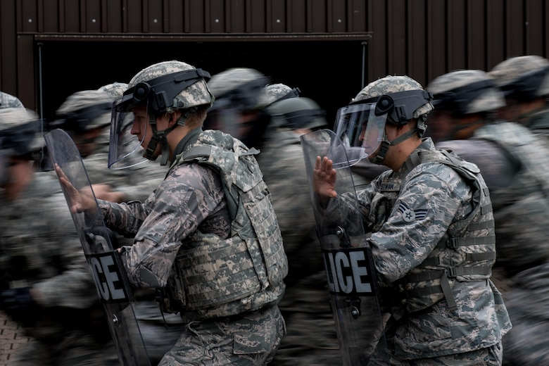 Airmen assigned to the 86th Security Forces Squadron perform formation maneuvers during confrontational management training at the 86th SFS training section on Ramstein Air Base, Germany, July 25, 2017. The formation practiceallowed patrolmen to keep their defenses while others moved forward to detain rioters. (U.S. Air Force photo/Senior Airman Devin Boyer)
