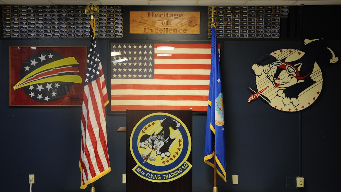 The front of the 48th Flying Training Squadron's Heritage Room shows the 48th Fighter Interceptor Squadron patch on the left of the American flag and the World War II 48th Pursuit Squadron patch designed by Disney Studios on the right and the current 48th Flying Training Squadron emblem below it. Walt Disney's team of artists created the patch along with many others for various units as a way to contribute to service members during World War II. (U.S Air Force photo by Airman 1st Class Beaux Hebert)