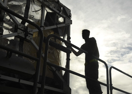 Silhouette of loadmaster loading Transportation Isolation System (TIS)