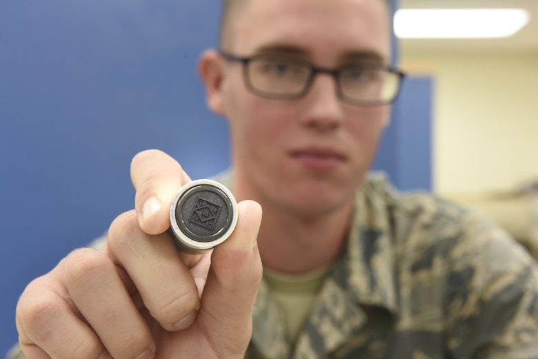 PMEL Airman holds up QC stamp
