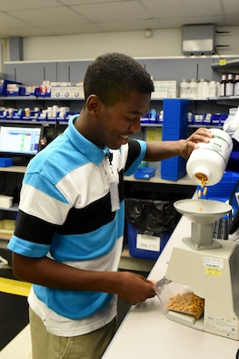 Jaylon Wallace, Goldsboro Summer Youth Employment Initiative Program participant, prepares a pre-pack of medication during his internship, July 19, 2017, at the 4th Medical Group pharmacy at Seymour Johnson Air Force Base, North Carolina. The youth program interns assigned to the 4th MDG pharmacy assisted with pre-packing medications, storing completed prescriptions and performing other pharmaceutical duties. (U.S. Air Force photo by Airman 1st Class Victoria Boyton)