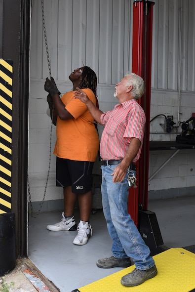 Emmanuel Scott-Persky (left), Goldsboro Summer Youth Employment Initiative Program participant, and Sammy Jones, 4th Civil Engineer Squadron welder, conduct routine maintenance on a vehicle repair shop roll up door, Aug. 3, 2017, at Seymour Johnson Air Force Base, North Carolina.