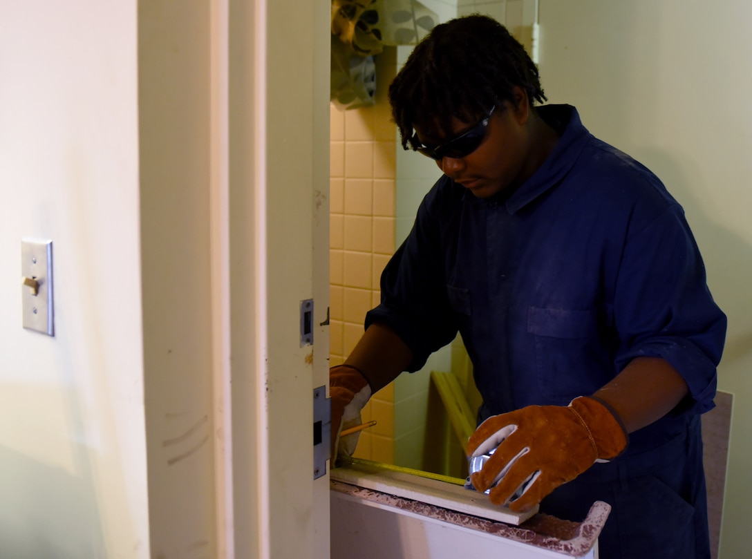 Tyriq Moore, Goldsboro Summer Youth Employment Initiative Program participant, repairs a dorm room shower basin during his internship, Aug. 3, 2017, at Seymour Johnson Air Force Base, North Carolina.