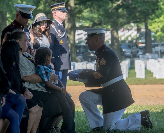 Sergeant Maj. Matthew R. Hackett, command sergeant major, Marine Barracks Washington D.C., passes the National Ensign to Sherry Jennings, spouse of Marine Sgt. Julian Kevianne, during a funeral for Kevianne at Arlington National Cemetery, Arlington, Va., Aug. 3, 2017. Kevianne, 31, was one of the 15 Marines and one Navy sailor who perished when their KC130-T Hercules crashed in Mississippi, July 10, 2017. He was part of the Marine Aerial Refueler Transport Squadron 452, Marine Aircraft Group 49, 4th Marine Air Wing, based out of Stewart Air National Guard Base in Newburgh, NY. (Official U.S. Marine Corps photo by Cpl. Robert Knapp/Released)