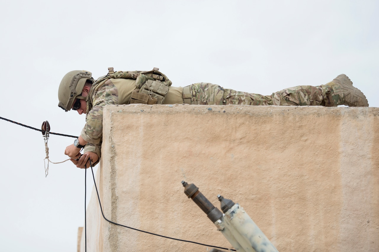 Air Force Senior Airman Jared Basham rigs a rope to open a door during the Raven's Challenge explosive ordnance disposal exercise at Camp Pendleton, Calif.
