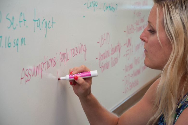 DAYTON, Ohio – Erin Nichols, a program manager on Team Wright-Patt, writes down project assumptions on a team whiteboard during a brainstorming session Aug. 2 as part of the Air Force Research Laboratory's Commander's Challenge 2017. The challenge this year is to remotely move 50 pounds of supplies to a location 30 miles away, delivering them to an area smaller than 400 square feet. (U.S. Air Force photo/John Harrington)