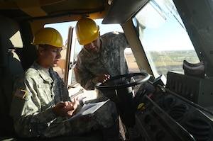 Soldiers in a military vehicle wearing hard hats