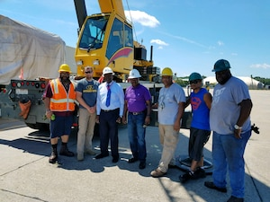 Left to right: The Pier Operations Team members: Lamarr Coles, Gilbert Gragg, Bobby Scarboro (Pier 8 Director), George Brackett (Stevedore Supervisor), Bernard Rawlings, Rugin Rex De Leon Sardon and George Walker, with the mobile crane used to lift the sonar dome.