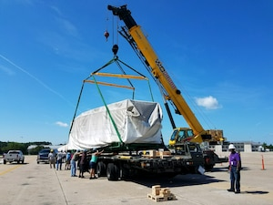 The DLA Distribution Norfolk Pier Operations Team assists the Norfolk Air Mobility Command Air Terminal to lift a 21-ton sonar dome in order to prepare it for flight in a C5 cargo aircraft.