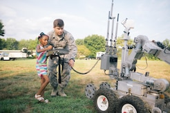 Senior Airman Paul Christiansen, 11th Civil Engineer Squadron explosive ordinance disposal journeyman, assists McKinley Foster, local resident, in operating a F6A EOD robot during a National Night Out event held in Clinton, Md., Aug. 1, 2017. The NNO event provided an opportunity for JBA to display its emergency response capabilities to the local community. (U.S. Air Force photo by Senior Airman Delano Scott)