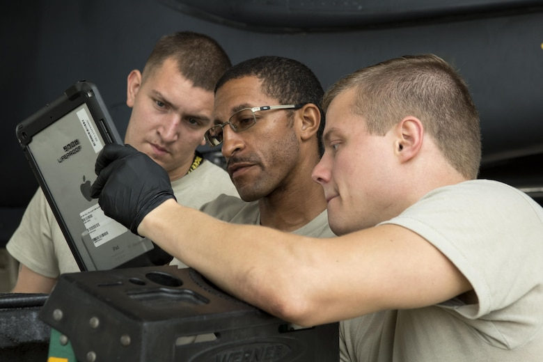 Staff Sgt. Joshua Cantrell (right), 4th Aircraft Maintenance Squadron avionics specialist, Tech. Sgt. Derek Mitchell and Airman 1st Class Zachary Brown, 4th AMXS engines specialists, review technical orders to trouble shoot an indication issue on an F-15E Strike Eagle, Aug. 3, 2017, at Seymour Johnson Air Force Base, North Carolina. In preparation for exercise Combat Hammer at Hill Air Force Base, Utah, Airmen from the 4th AMXS prepped jets to participate in the two-week exercise. (U.S. Air Force photo by Airman 1st Class Shawna L. Keyes)