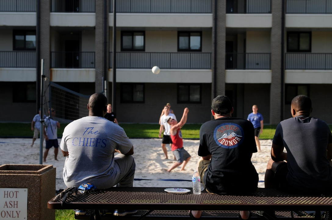 Spectators watch dorm residents and Keesler chief master sergeants play volleyball during the 2017 Dorm Bash at the Biloxi Hall courtyard August 1, 2017, on Keesler Air Force Base, Miss. The Dorm Bash was sponsored by the Keesler Chiefs Group to provide an opportunity for Keesler dorm residents to spend time together in fellowship. The chief master sergeants took home the Battle of the Bash Dragon award. (U.S. Air Force photo by Airman 1st Class Suzanna Plotnikov)