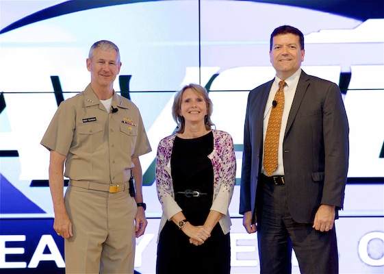 "Image: WASHINGTON (July 19, 2017) - Dr. Mary Ann Cummings is flanked by Vice Adm. Thomas Moore, NAVSEA commander, and Jim Smerchansky, NAVSEA executive director at the NAVSEA Excellence Awards and Commander's Awards for Innovation ceremony. She is pictured after receiving the NAVSEA Scientist of the Year Award for a modeling and simulation innovation called Orchestrated Simulation through Modeling (OSM) at the NAVSEA Excellence Awards and Commander's Awards for Innovation ceremony. ""We can create simulations that show what could happen and take data from an exercise to show how that exercise might play out as a real event,"" said Cummings. OSM is now available to the Department of Defense for its programs and exercises.  (U.S. Navy photo/Released)"