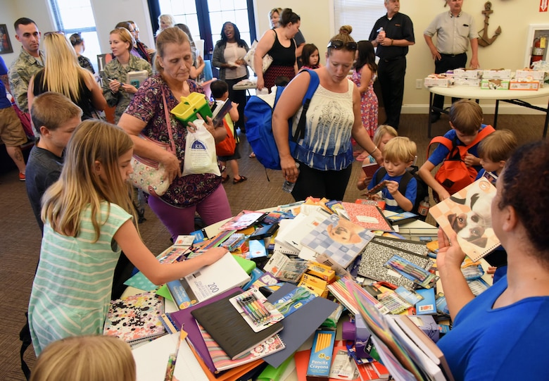 Military families gather assorted school supplies in the Bay Ridge Community Center for a back-to-school event sponsored by Operation Homefront Aug. 1, 2017, on Keesler Air Force Base, Miss. More than 4,000 items and 300 backpacks were donated to 120 military families. (U.S. Air Force photo by Kemberly Groue)