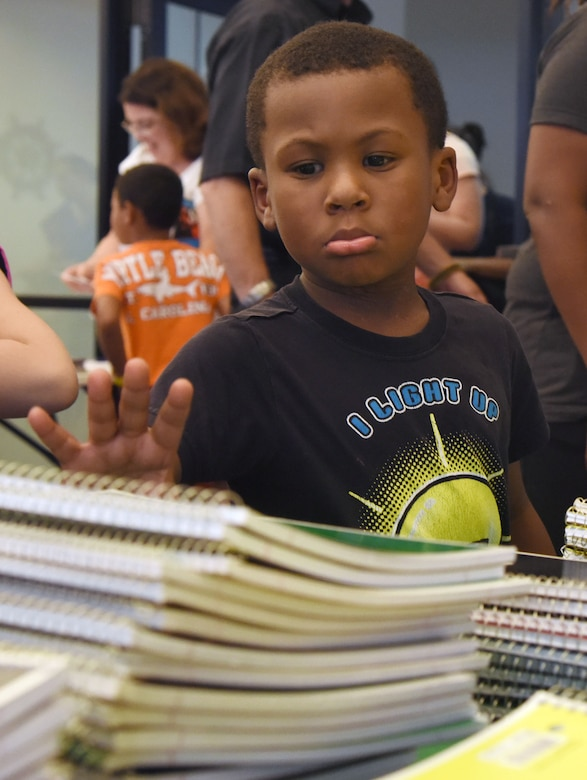 James White, son of Tech. Sgt. Charles White, Jr., 335th Training Squadron military training leader, reaches for a notebook during a back-to-school event sponsored by Operation Homefront in the Bay Ridge Community Center Aug. 1, 2017, on Keesler Air Force Base, Miss. More than 4,000 items and 300 backpacks were donated to 120 military families. (U.S. Air Force photo by Kemberly Groue)