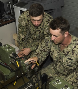 Electronics Technician 3rd Class Codie Flanagan and Electronics Technician 2nd Class Anthony Juarez, assigned to Naval Mobile Construction Battalion (NMCB) 1, adjust frequency codes on a GRC-234 high-frequency base station at Naval Base Guam July 27, 2017. These tests give NMCB 1 Sailors the opportunity to perform quality assurance checks on their system's maximum range and communication quality with Port Hueneme, Calif. NMCB 1 provides expeditionary construction and engineering support to expeditionary bases and responds to humanitarian assistance disaster relief requests.