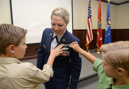 : U.S. Air Force Tech. Sgt. Courtney, has her remotely piloted aircraft pilot wings pinned on by her sons David and Riley during the 558th Flying Training Squadron's Undergraduate Remotely Piloted Aircraft Training Course graduation August 4, 2017, at Joint Base San Antonio-Randolph, Texas. Tech. Sgt. Courtney is the first-ever enlisted female to qualify as an RPA pilot. Name badges were blurred due to Air Force limits on disclosure of identifying information for RPA operators. (U.S. Air Force Illustration by Tech. Sgt. Ave I. Young)
