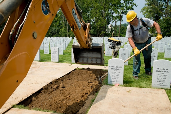 A grave digger buries the remains of 2nd Lt. Charles E. Carlson at the Indiantown Gap National Cemetery in Annville, Penn., Aug. 4, 2017. Carlson's grave is one of several thousand at the 677 acre cemetery. (U.S. Air Force photo/Staff Sgt. Jensen Stidham)