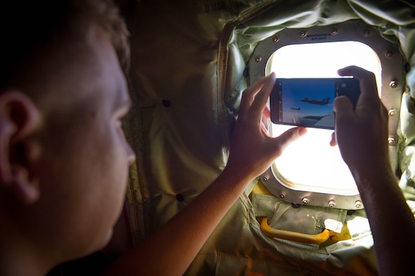 An Airman assigned to the 62nd Fighter Squadron, Luke Air Force Base, Ariz, takes a picture of F-35A Lighting IIs from an Arizona National Guard KC-135 Stratotanker Aug. 4, 2017. Several of the approximately 50 Airmen from the 62nd FS, on their way to a funeral for 2nd Lt. Charles E. Carlson, had never seen the F-35 from the air. (U.S. Air Force photo/Staff Sgt. Jensen Stidham)