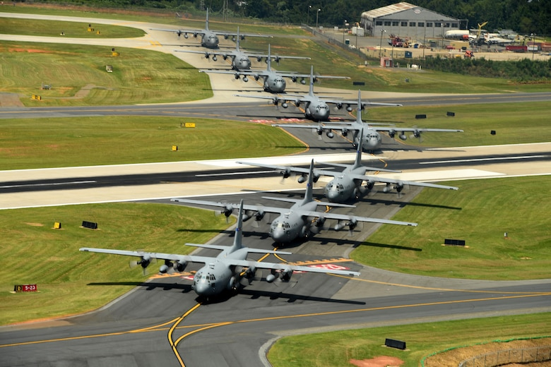 Eight C-130 aircraft taxi down the runway