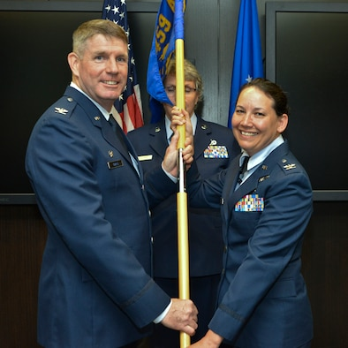 Col. David Owens, commander, 459th Air Refueling Wing, passes the squadron guidon to Col. Kimberly McCue, new commander, 459th Aeromedical Staging Squadron, Joint Base Andrews, Maryland on August  5, 2017. McCue will be responsible for the training and readiness of 140 medical personnel who ensure patients are medically and administratively prepared for flight. (U.S. Air Force photo/Tech. Sgt. Erica J. Knight)