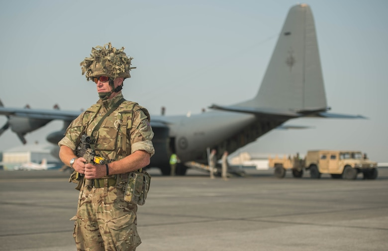Royal Air Force aircraftsman in full uniform for exercise is standing on the flightline