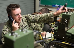 Electronics Technician 2nd Class Anthony Juarez and Electronics Technician 3rd Class Codie Flanagan, assigned to Naval Mobile Construction Battalion (NMCB)1,  adjust frequency codes on a GRC-234 high-frequency base station at Naval Base Guam July 27, 2017. These tests give NMCB 1 Sailors the opportunity to perform quality assurance checks on their system's maximum range and communication quality with Port Hueneme, Calif. NMCB 1 provides expeditionary construction and engineering support to expeditionary bases and responds to humanitarian assistance disaster relief requests.