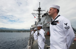 Sonar Technician (Surface) 2nd Class Matthew Fryer, assigned to the Arleigh Burke-class guided-missile destroyer USS Barry (DDG 52), stands at parade rest while pulling into Guadalcanal for a port visit to commemorate the 75th anniversary of the Guadalcanal Campaign. The 75th commemoration is a tribute to the courage, service, and sacrifice of those who fought in the Guadalcanal Campaign of World War II.
