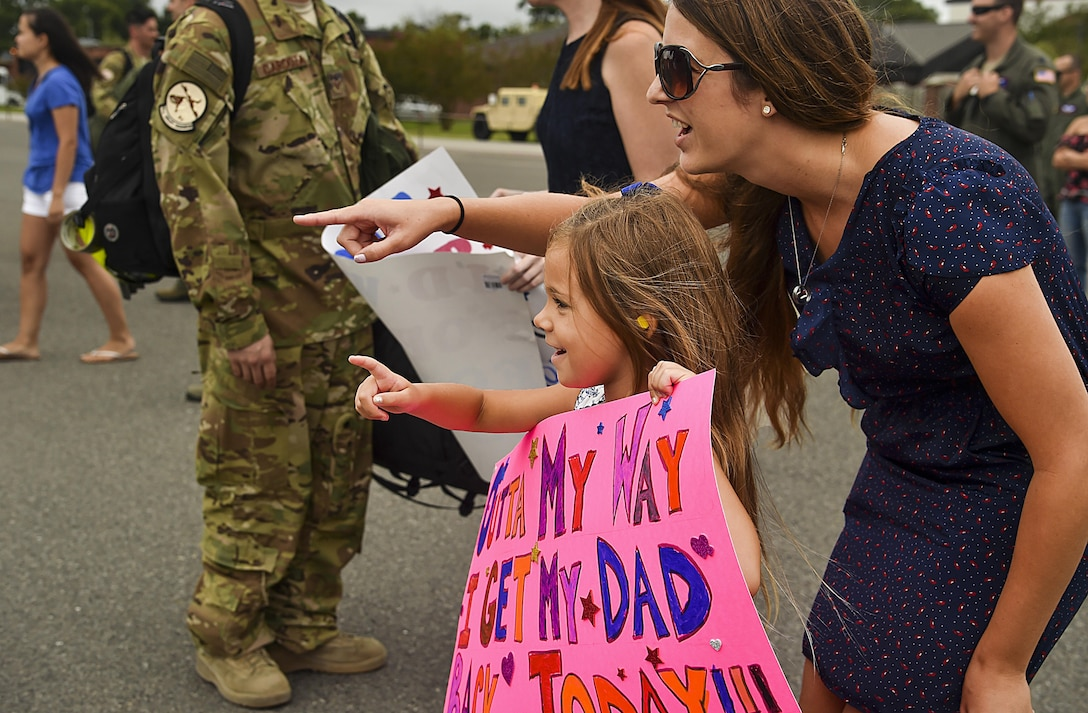 Hailey Fatjo, left, and Stacey Fatjo, right, wife and daughter of a returning Charleston deployer, point in excitement as he gets off a plane at Joint Base Charleston, S.C., Aug. 8, 2017.