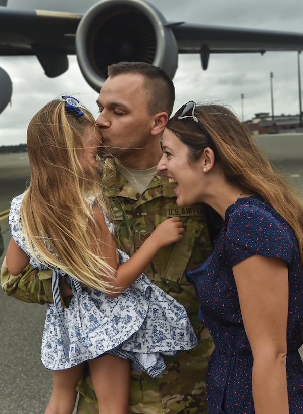 Tech. Sgt. Jason Fatjo, 14th Airlift Squadron loadmaster, embraces his family after returning from a deployment at Joint Base Charleston, S.C., Aug. 8, 2017.