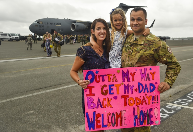Tech. Sgt. Jason Fatjo, 14th Airlift Squadron loadmaster, and his family hold his welcome home sign at Joint Base Charleston, S.C., Aug. 8, 2017. Fatjo returned from a deployment to Southwest Asia.