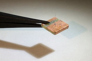 Tweezers hold a small square platform with a artificial hair sensor.