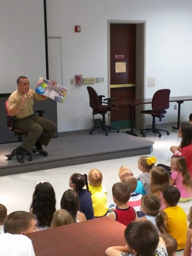 Captain Trodden, Operations Officer for PMO, reading to the boys and girls at Ellis Hall. Security Battalion personnel were on hand to read books and participate in a show-and-tell to youngsters who attended for Police and Firefighter Storytime.