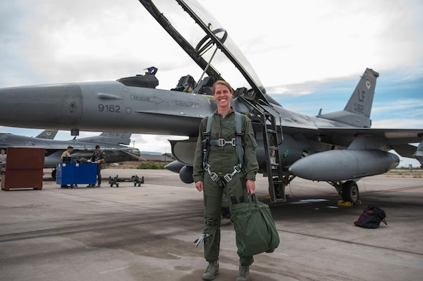 2nd Lt. Taylor O'Neil, Uniformed Services University of Health Sciences medical student, poses in front of an F-16 Fighting Falcon prior to take off at Holloman Air Force Base, N.M., July 28, 2017. Members from the 54th Fighter Group hosted USU medical students during the summer operational experience program, which is for first-year medical students transitioning to their second year of medical school. Future flight surgeon hopefuls were given familiarization flights as part of an inside look into what pilots go through in order to better provide care for pilots. (U.S. Air Force photo by Senior Airman Chase Cannon)