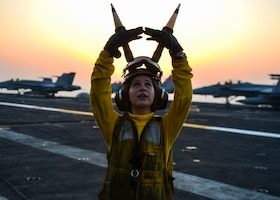 Aircraft carrier sailor signals to pilot