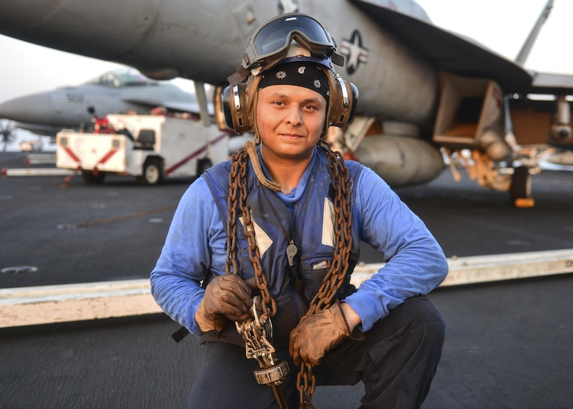 Sailor holds chains on aircraft carrier flight deck