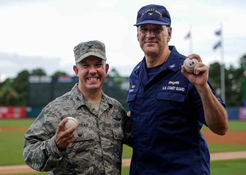 U.S. Air Force Col. Patrick Winstead, 437th Airlift Wing vice commander, left, and U.S. Coast Guard Capt. Gregory Stump, Coast Guard Sector Charleston commander, right, hold up their souvenir baseballs after throwing the ceremonial first pitches during the Charleston RiverDogs Military Appreciation Night at Joseph P. Riley Jr. Park, Aug. 3, 2017.