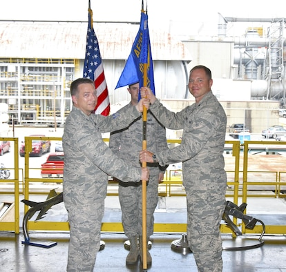 Lt. Col. David Hoffman, right, becomes director of the Flight Systems Combined Test Force (TSTW) during a Change of Directorship ceremony July 21 inside the Model Installation Building, part of the Propulsion Wind Tunnel Test Facility, at Arnold Air Force Base, Tennessee. Col. Timothy West, (left) chief of the AEDC Test Operations Division, passes the TSTW guidon to Hoffman as 1st Lt. Roy Fisher, looks on. The Flight Systems CTF provides aerodynamic ground-test capabilities from low subsonic to hypersonic speeds in various wind tunnels and supports Department of Defense, U.S. industry and international aerospace programs. (U.S. Air Force photo/Rick Goodfriend)