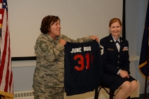 U.S. Air National Guard Chief Master Sgt. Josephine A. Iennaco, the 157th Medical Group superintendent, presents Senior U.S. Air National Guard Master Sgt. June Fonteyne, a health systems technician with the 157th MDG, a sweatshirt with her nickname and number of total years of service during her retirement ceremony August 5, 2017 at Pease Air National Guard Base, N.H. In lieu of a traditional shadow box, Fonteyne was presented a collection of small gifts that represented her passions, hobbies and the four seasons of New Hampshire. (Air National Guard Photo by Senior Airman Ashlyn J. Correia)