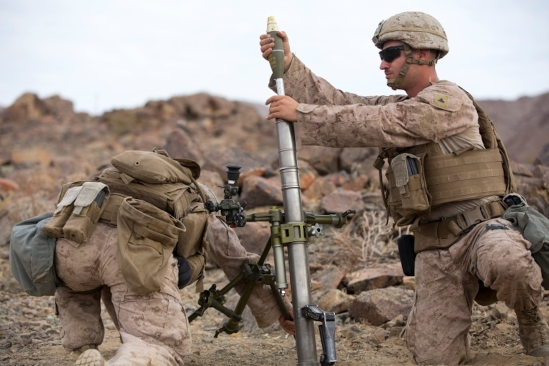 Lance Cpl. Kyle Hollenback, mortarman, 1st Battalion, 1st Marine Regiment, loads a while Pfc. Sean Carlson, mortarman, 1/1, stabilizes the stand during an individual training exercise at Range 410A aboard the Marine Corps Air Ground Combat Center, Twentynine Palms, Calif., July 25, 2017. 1/1 is based out of Marine Corps Base Camp Pendleton, and is serving as part of the GCE during ITX 5-17. (U.S. Marine Corps photo by Pfc. Margaret Gale)