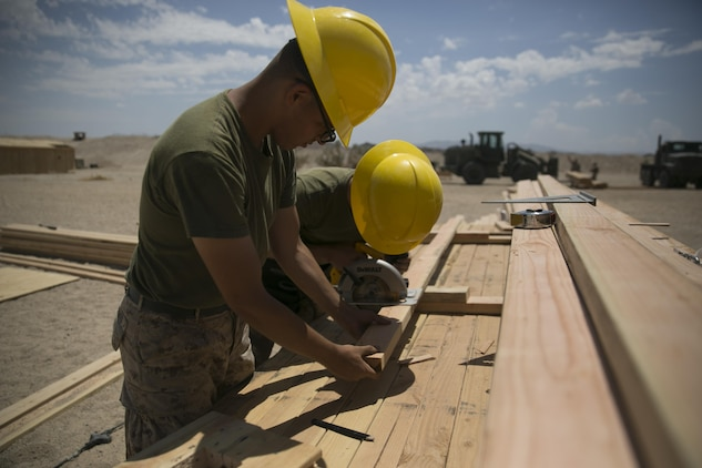 Marines with the engineer platoon for Marine Wing Support Squadron 272, cut wood for a Southwest Asia hut aboard the Combat Center during Integrated Training Exercise 5-17, July 29, 2017. MWSS-272 is supporting the Aviation Combat Element of the ITX. The ACE conducts offensive, defensive, and all other air operations to support the MAGTF mission . (U.S. Marine Corps photo by Cpl. Medina Ayala-Lo)
