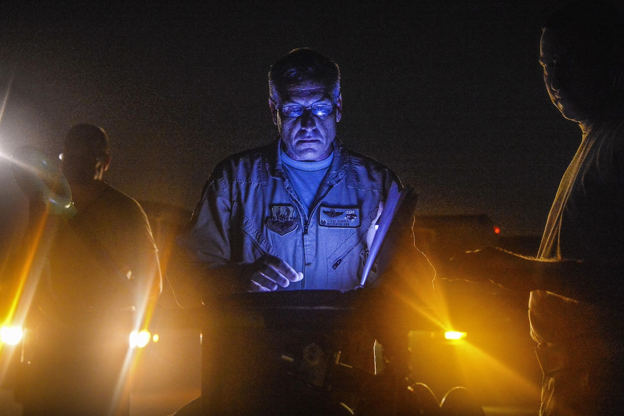 An airman reviews records at night as lights shine from below.