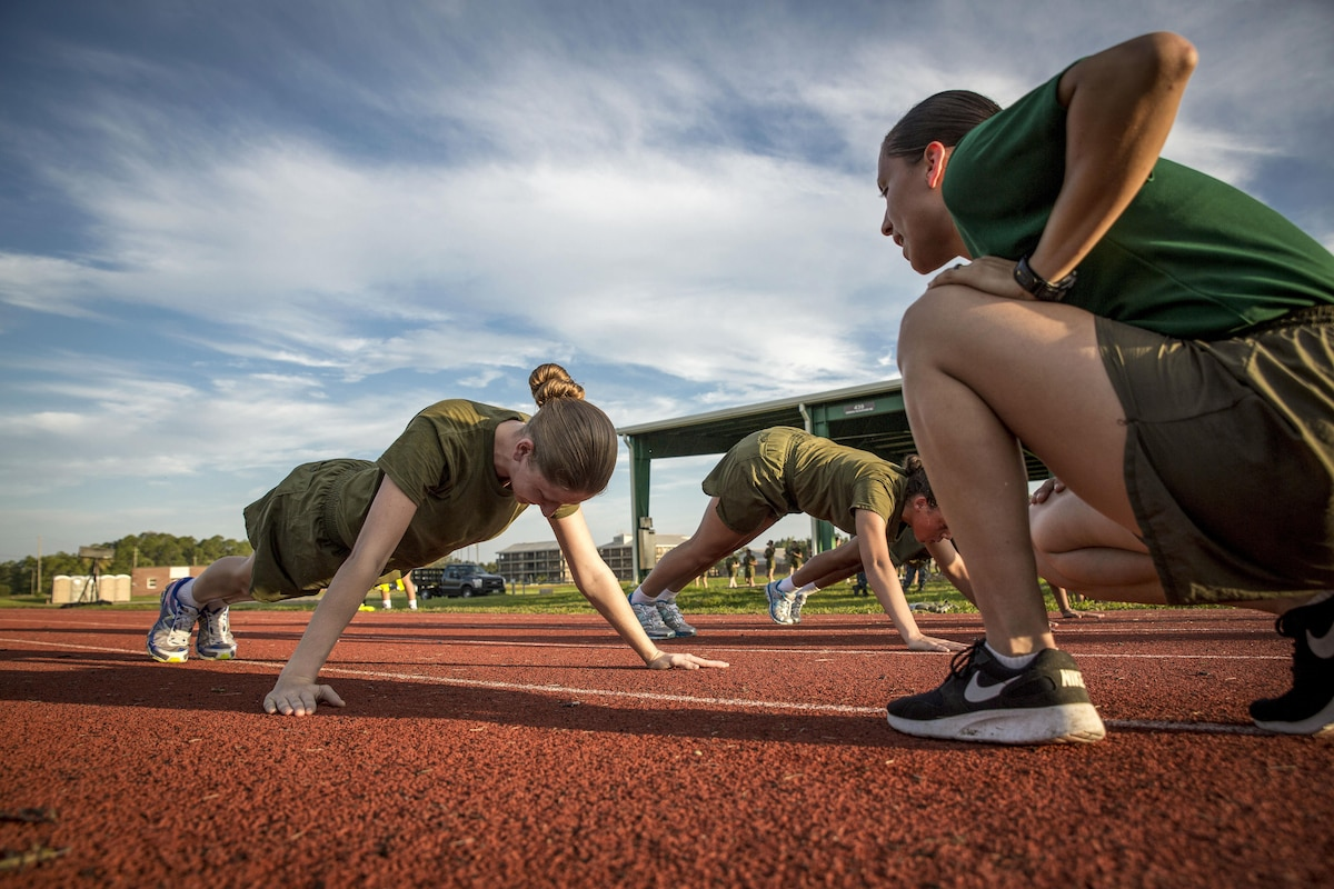 An instructor monitors as Marine Corps recruits do pushups.