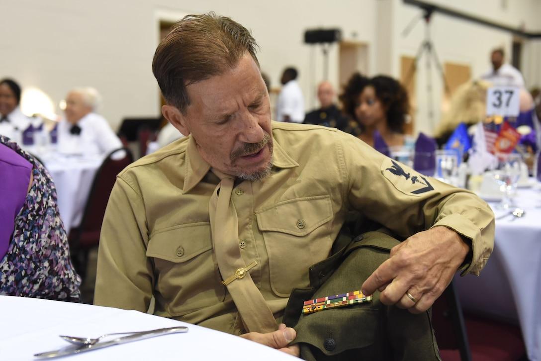Jack Hanley, Purple Heart recipient, explains each decoration on his uniform, Aug. 4, 2017, at the Goldsboro/Wayne Purple Heart Foundation Purple Heart banquet in Goldsboro, North Carolina.