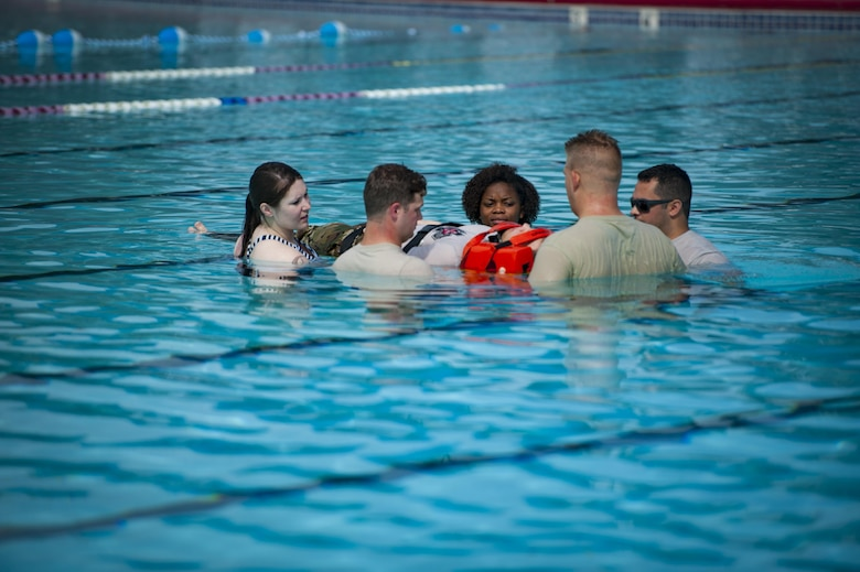 Airmen from the 23d Medical Group transport a simulated victim out of the pool during emergency medical technician refresher training, Aug. 4, 2017, at Moody Air Force Base, Ga. During the five-day refresher training, 23d Medical Group Airmen learned how to perform cardiac arrest management, airway management, hemorrhage control and spinal immobilization. At the end of the course, Airmen were evaluated on their ability to perform medical and trauma patient assessments based on various emergency circumstances. (U.S. Air Force photo by Airman 1st Class Lauren M. Sprunk)
