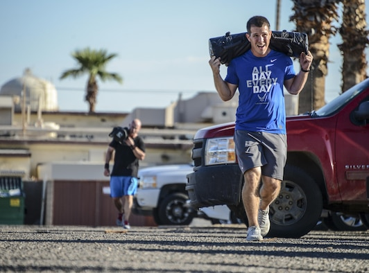 Master Sgt. Douglas Teutsch, 56th Communications Squadron client services section chief, runs with a 40 pound bag on his shoulders during the 31 heroes competition held at Luke Air Force Base, Ariz., August 4, 2017. The event was held in the Combat PT tent and consisted of a variation of thrusters, rope climbs, box jumps and a run. (U.S. Air Force photo/Airman 1st Class Caleb Worpel)